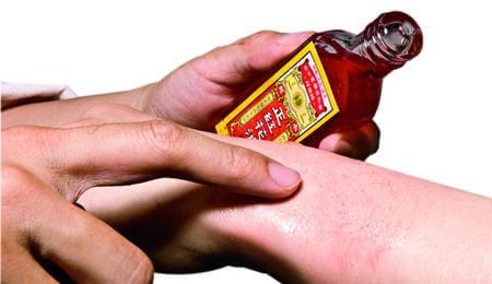 Applying red flower oil on hands